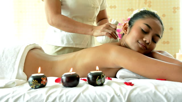 close up of beautiful woman having back massage by massage therapist on the massage bed in spa salon. happy attractive girl with tropical flower relaxing and massaging in spa resort - health spa stock videos and b-roll footage