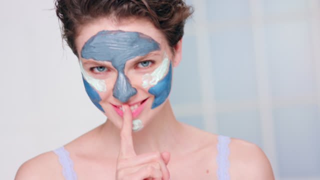 close up of beautiful woman wearing a blue clay face mask. - color block stock videos and b-roll footage