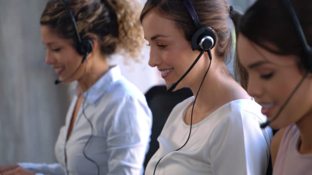 close up of beautiful women working at a call center receiving calls very cheerfully - headset stock videos & royalty-free footage