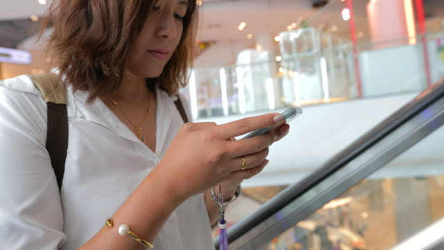 close up of beautiful young woman attractive on mall escalator with using mobile smart phone at shopping mall - clothes shop stock videos & royalty-free footage