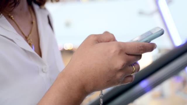 Närbild på vacker ung kvinna attraktiv på mall rulltrappa med Smart mobiltelefon på köpcentrum