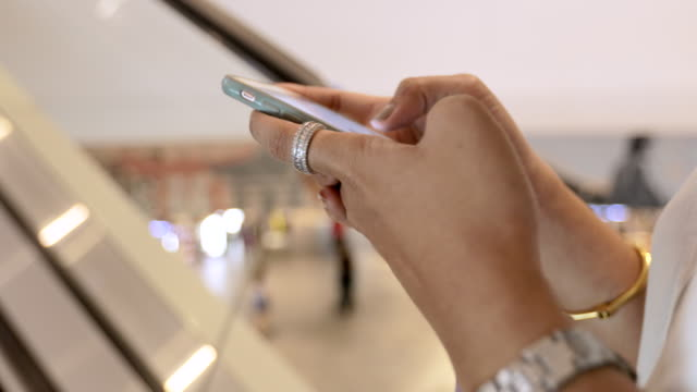 Close up of Beautiful young woman attractive on mall escalator with using Mobile Smart Phone at Shopping Mall