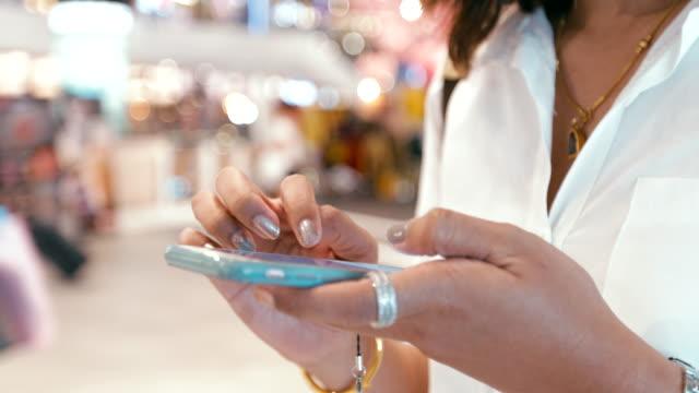 Närbild på vacker ung kvinna attraktiv med hjälp av Smart mobiltelefon på köpcentrum