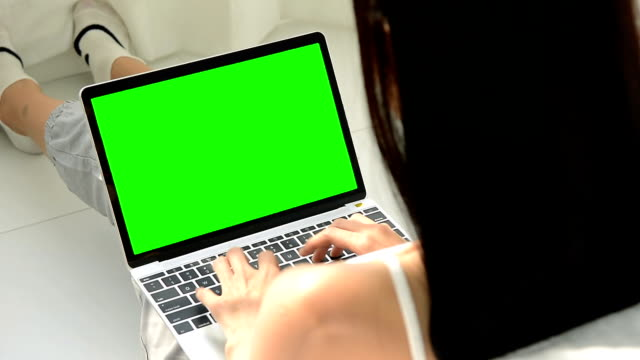 close up of beautiful young woman using a laptop computer with greenscreen monitor - keyable stock videos & royalty-free footage