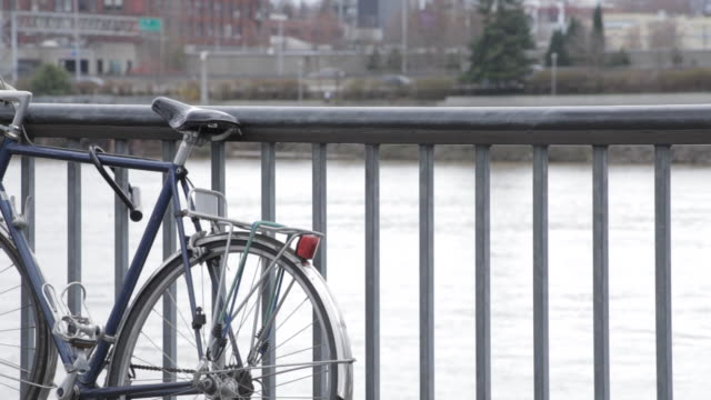 close up of bike against railing with water and buildings and trees, cars passing by and person walks past - portland oregon bike stock videos & royalty-free footage