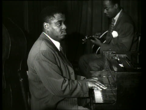 B/W close up of black man playing piano / guitarist in background / Art Tatum