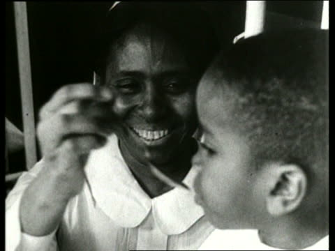 b/w close up of black woman feeding young boy with spoon / sound - single mother stock videos & royalty-free footage
