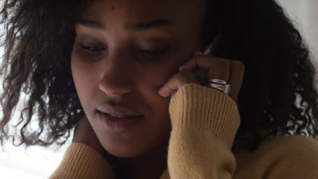 close up of black young woman on a serious phone call using her smartphone - worried stock videos & royalty-free footage