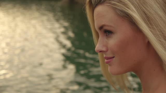 vídeos de stock, filmes e b-roll de close up of blond woman's face as she sits beside water/marbella region, spain - só mulheres jovens
