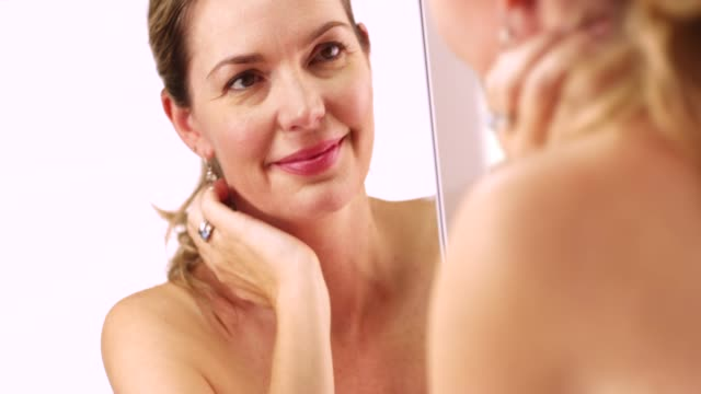 vídeos de stock e filmes b-roll de close up of blonde caucasian woman touching her eyes in mirror - mulheres maduras