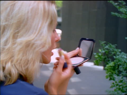 rear view close up of blonde woman looking in compact + putting on lipstick outdoors / nyc - lipstick stock videos & royalty-free footage