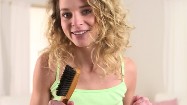 Close up of blonde woman singing with hairbrush