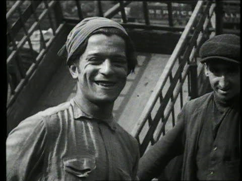B/W 1927 close up of blue collar worker in hat smiling / another in background / Paris, France
