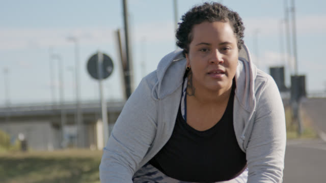 vidéos et rushes de close up of body positive overweight women is doing workout on racing bike - femme ronde