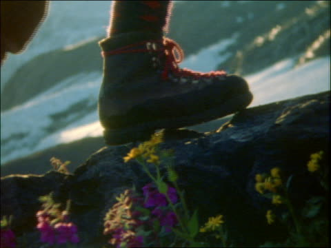 close up of boots of mountain climber walking on rocks