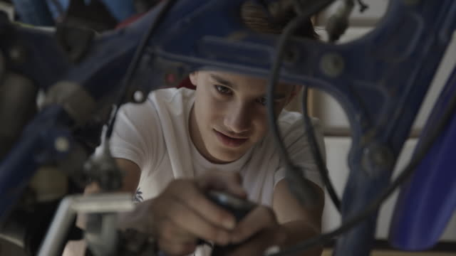 vídeos de stock e filmes b-roll de close up of boy grimacing while repairing motorcycle / lehi, utah, united states - lehi