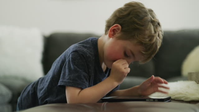 close up of boy reading digital tablet and picking nose / pleasant grove, utah, united states - nursery school child stock videos & royalty-free footage