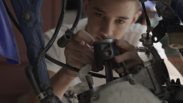 vídeos de stock e filmes b-roll de close up of boy repairing motorcycle piston / lehi, utah, united states - lehi