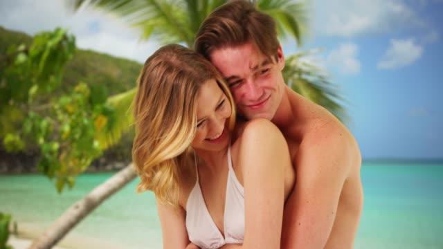 vídeos y material grabado en eventos de stock de close up of boyfriend hugging girlfriend from behind on beach in the caribbean - bañador de natación