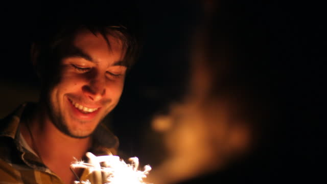 close up of boyfriend lighting sparkler over the shoulder of girlfriend - boyfriend stock videos & royalty-free footage
