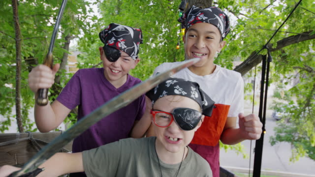 Close up of boys holding swords playing pirate in tree / Provo, Utah, United States