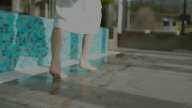 close up of boys legs while in bathrobe running around swimming pool - standing water stock videos & royalty-free footage