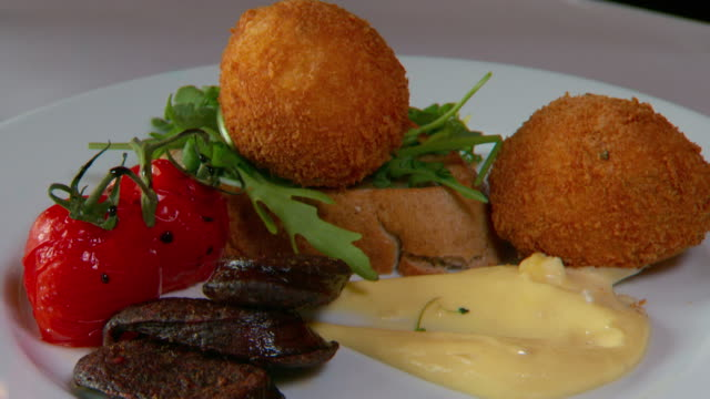 close up of breakfast brunch meal of grilled tomatoes, smoked chorizo sausage, crumbed croquettes, rocket, sourdough toast and hollandaise sauce. - chorizo stock videos & royalty-free footage