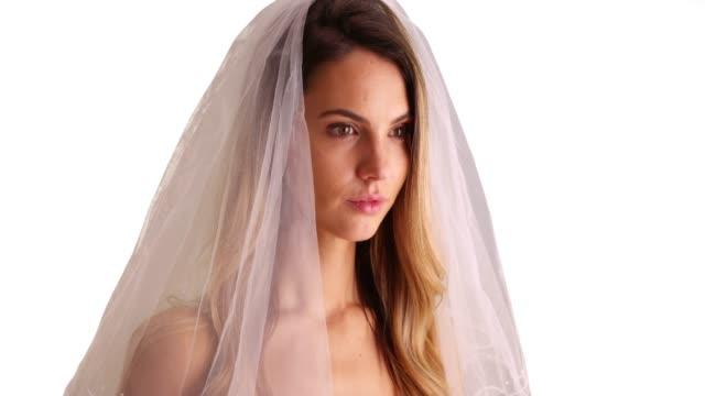 vidéos et rushes de close up of bride wearing veil, looking off camera in studio with copyspace - robe blanche