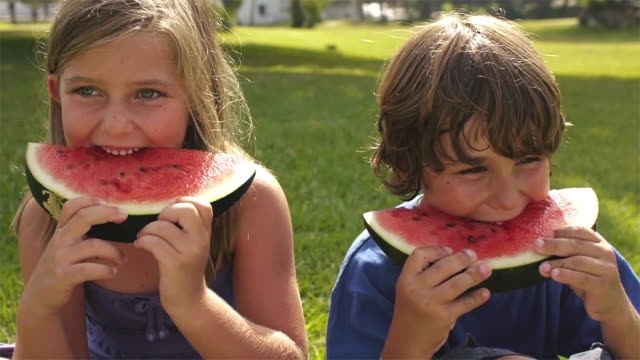 Close up of brother and sister eating watermelon/Marbella region, Spain