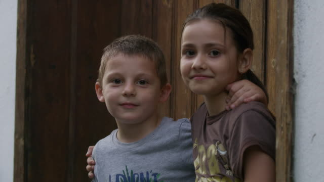 Close up of brother and sister hugging in doorway / Veliko Tarnovo, Bulgaria