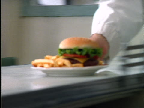 close up of burger + fries on dish sliding on diner counter