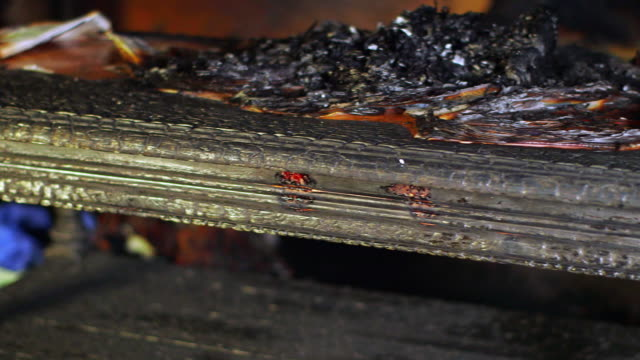Close up of burnt and blackened books and furniture after a fire
