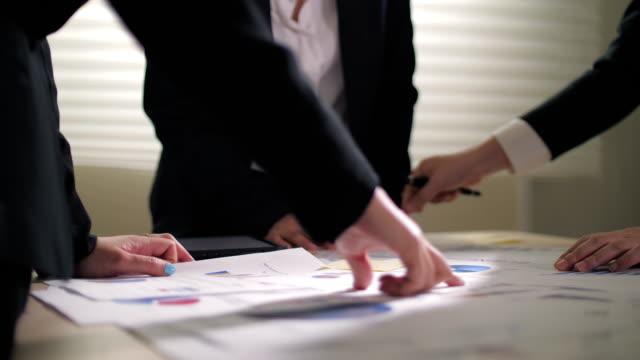 vídeos de stock e filmes b-roll de close up of business hands meeting and brainstorming in office with graph and document - filme de ação