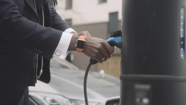 vídeos y material grabado en eventos de stock de close up of business man charging electric car at charging station - coche eléctrico coche alternativo