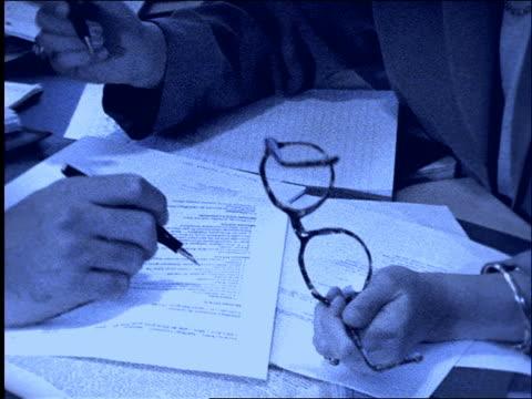 vídeos y material grabado en eventos de stock de b/w close up of businessman's and woman's hands with pens on paper / slow motion / tilt up to woman - imagen virada