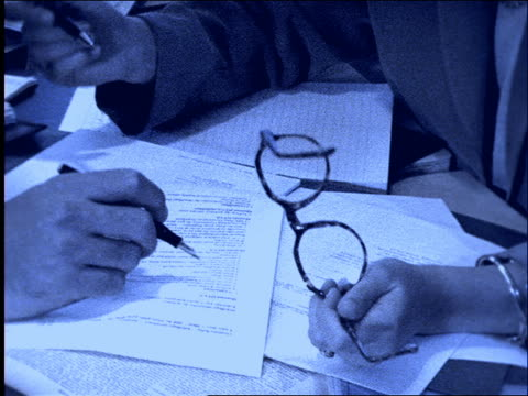 vídeos y material grabado en eventos de stock de b/w close up of businessman's and woman's hands with pens on paper / tilt up to woman - imagen virada