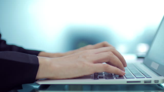 Close up of Businesswoman Hands typing on laptop keyboard on blue blurred background