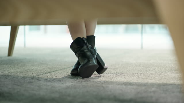 Close up of businesswoman's feet under desk in office