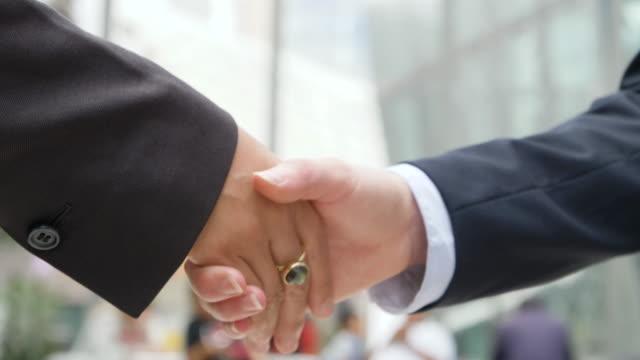 Close up of businesswomen shake hands.
