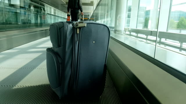close up of carry-on luggage placed on moving walkway in airport - carry on luggage stock videos and b-roll footage