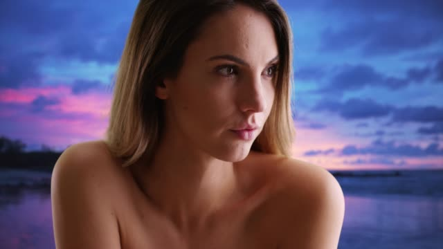 Close up of Caucasian female with bare skin looking off camera on beach at dusk