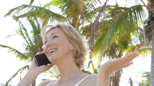 Close up of Caucasian woman under palm trees on cell phone