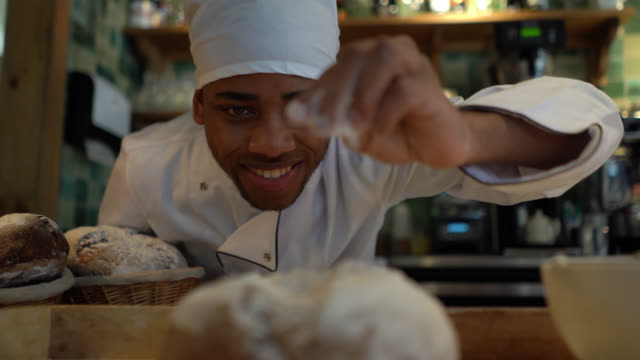 close up of cheerful chef sprinkling flour on bread at a bakery - sprinkling stock videos & royalty-free footage