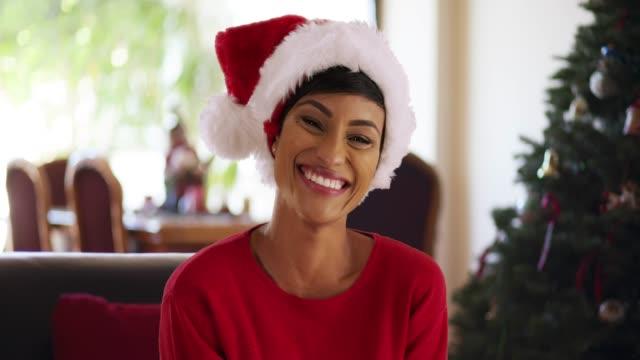 close up of cheerful woman on christmas morning smiling at camera - santa hat stock videos & royalty-free footage