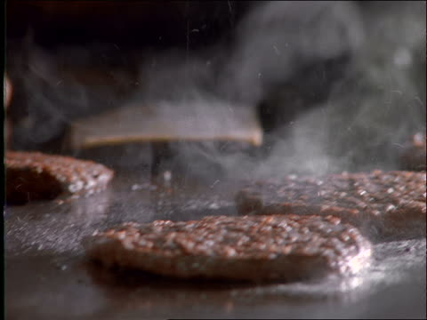 vídeos de stock, filmes e b-roll de close up of cheese being put on hamburgers on grill - grill
