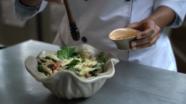 close up of chef adding a dressing to a delicious salad at the kitchen's restaurant - salad dressing stock videos & royalty-free footage