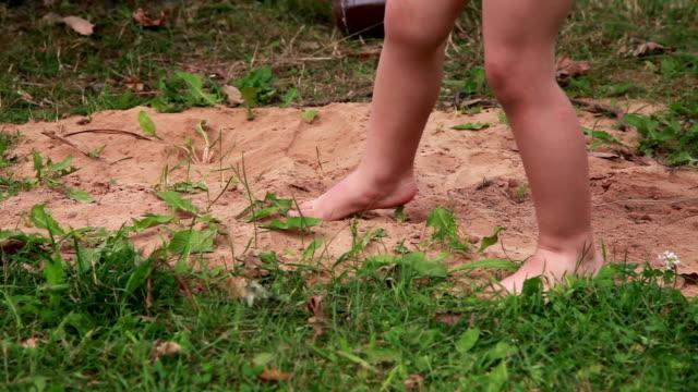 vidéos et rushes de gros plan de l'enfant de sable de coups de pied - donner un coup de pied