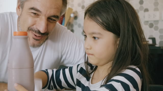 close up of child wiping chocolate milk bottle with father guiding her. - chocolate milk stock videos & royalty-free footage