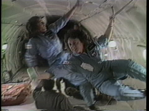 close up of christa mcauliffe floating with one hand on the roof of the training facility where she is preparing for being in a weightless... - other stock videos & royalty-free footage