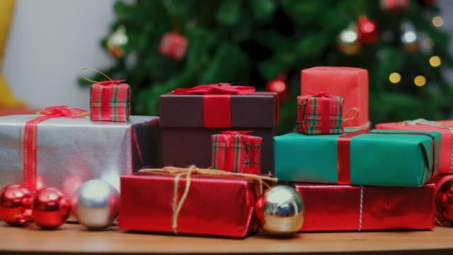 クリスマスプレゼントのクローズアップ、木製の床の背景にギフトボックス、スローモーション - ギフトショップ点の映像素材/bロール